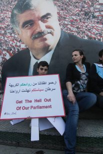 Some felt that the protests evoked the memory of 2005's Cedar Revolution, which kicked Syria out of Lebanon and was sparked by the assassination of former Prime Minister Rafik Hariri, pictured commemorated in a poster behind the demonstrators.