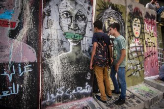Youngsters peer through a wall erected by the government in response to the #YouStink protests