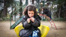 Yamman and her sister play in a park in Athens. Her family is now living rent-free in a flat provided by a Greek family